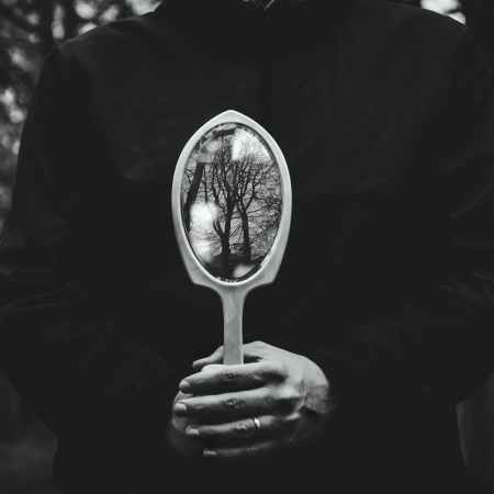 person holding hand mirror | gothic noir