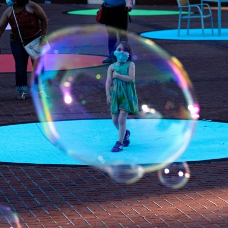 children playing with bubbles on street